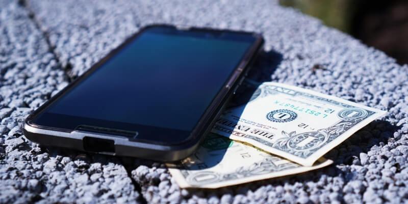 Ein Mobiltelefon und Geldscheine liegen auf einem Tisch.