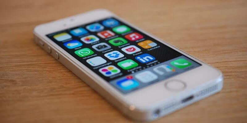 Weißes Smartphone mit vielen Apps auf dem Display.