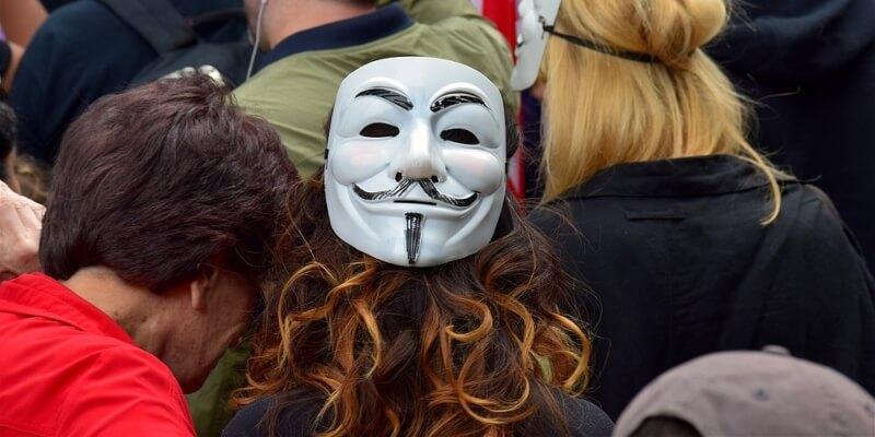 Demonstrantin mit Guy-Fawkes-Maske