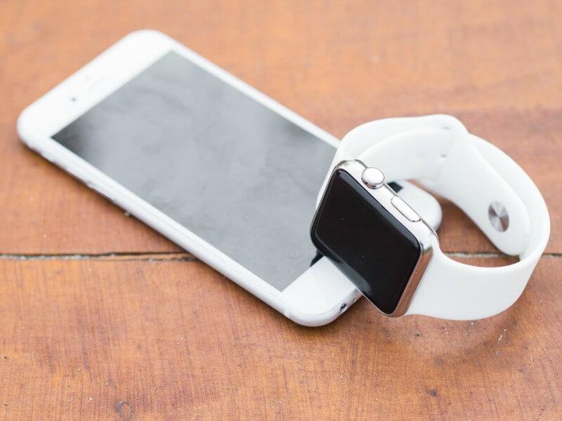 Weißes iPhone mit weißer Apple Watch auf einem Tisch.